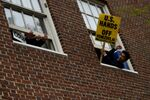 A man holds a sign outside the window of the Venezuelan embassy which is occupied by Nicolas Maduro supporters as Venezuelan opposition leader Juan Guido's envoy to the United States Carlos Vecchio speaks outside in Washington, U.S., May 1, 2019