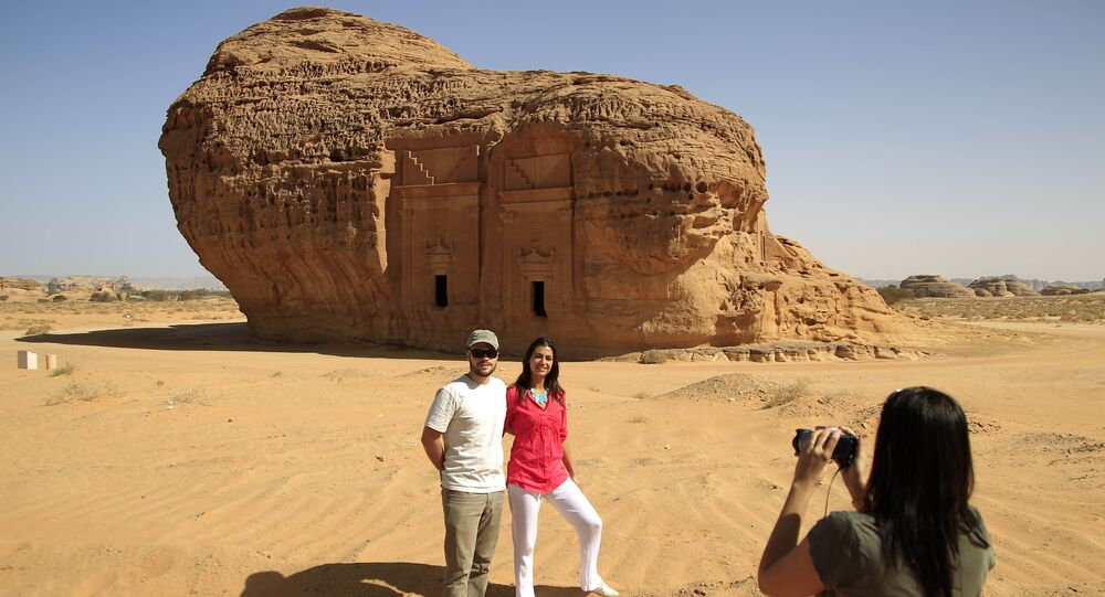 In this photograph made on Thursday, May 10, 2012, a foreign tourist takes picture of couple in the desert archaeological site of Madain Saleh, in Al Ula city, 1043 km (648 miles) northwest of the capital Riyadh, Saudi Arabia
