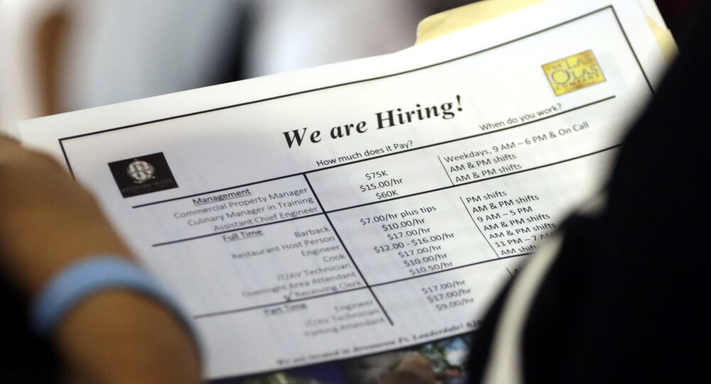 A job applicant looks at job listings for the Riverside Hotel at a job fair hosted by Job News South Florida