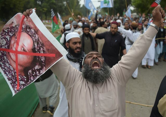 In this file photo taken on November 2, 2018 a Pakistani supporter of the Ahle Sunnat Wal Jamaat (ASWJ), a hardline religious party, holds an image of Christian woman Asia Bibi during a protest rally following the Supreme Court's decision to acquit Bibi of blasphemy, in Islamabad