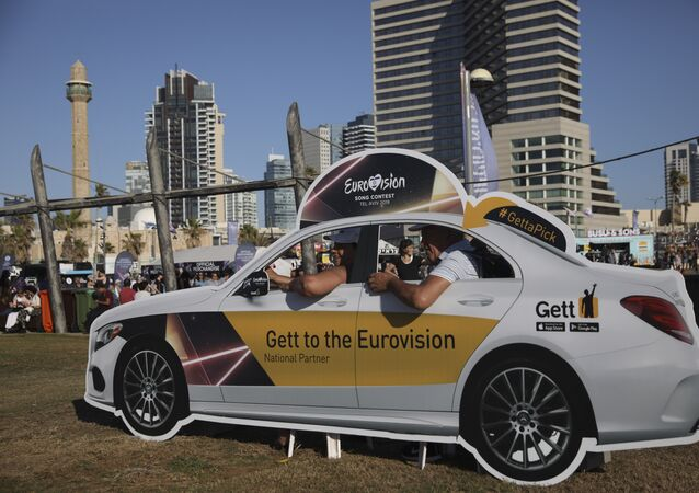 People pose in a cutout taxi cab ahead of the 2019 Eurovision Song Contest in Tel Aviv, Israel, Monday, May 13, 2019