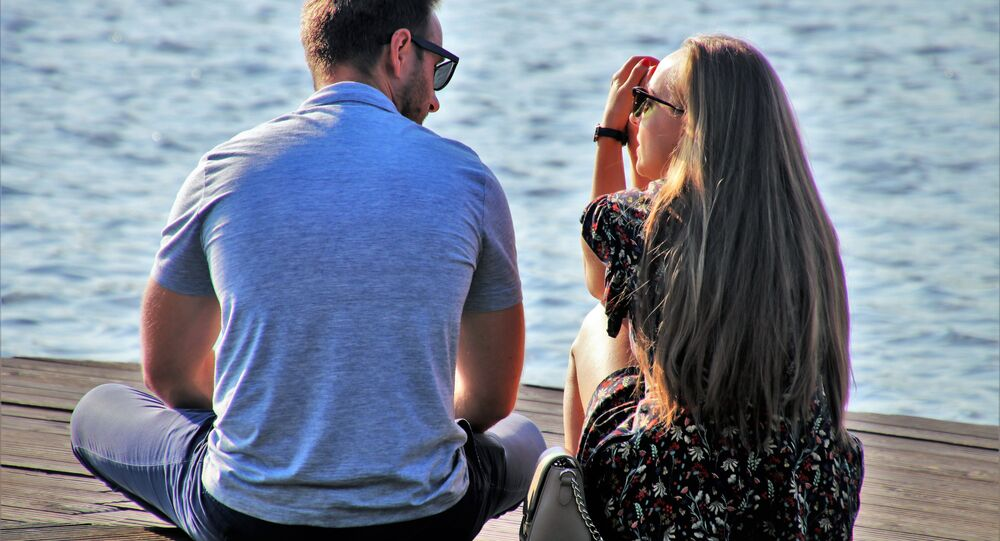 Couple talking while sitting on a dock