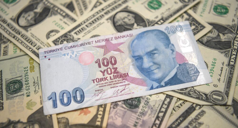 A picture taken in Istanbul on May 23, 2018 shows Turkish lira and US dollars banknotes