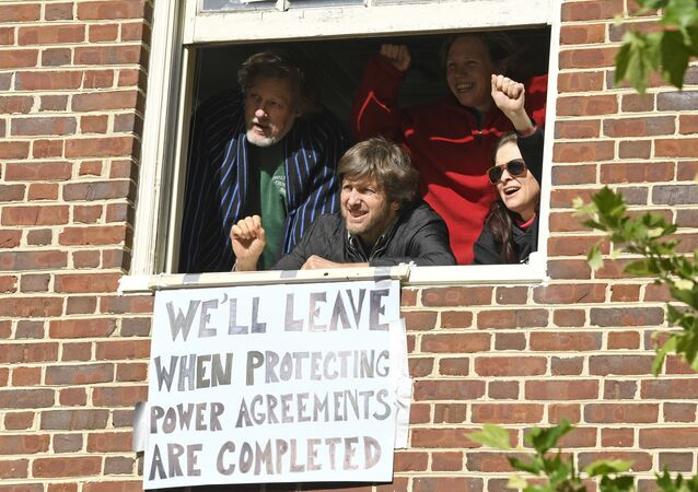 The four activists inside the Venezuelan embassy in Washington look outside the window from a second floor on Tuesday, May 14, 2019. Clockwise from left: Kevin Zeese, Margaret Flowers, Adrienne Pine, and David Paul.