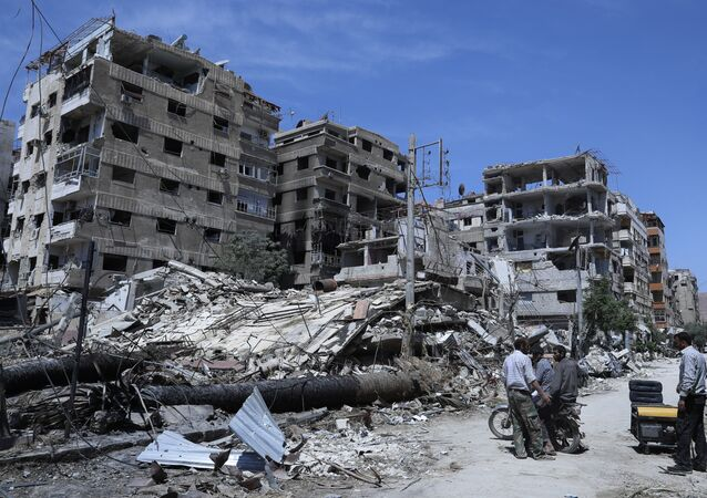 Syrians stand in front of damaged buildings in the Damascus suburb of Douma, the site of an alleged chemical weapons attack, 16 April 2018