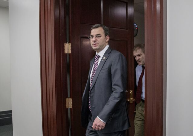 File-This March 28, 2017, file photo shows Rep. Justin Amash, R-Mich., followed by Rep. Jim Jordan, R-Ohio, leaving a closed-door strategy session with Speaker of the House Paul Ryan, R-Wis. A top aide to President Donald Trump is urging the primary defeat of a conservative House member from Michigan. A tweet Saturday, April 1, 2017, by White House social media director Dan Scavino Jr., comes two days after Trump threatened conservative lawmakers who thwarted a House vote on health care legislation. Scavino targeted Amash, a member of the conservative Freedom Caucus criticized by Trump.