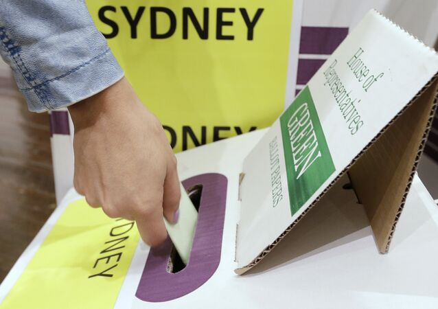 A voter casts their ballot at the Town Hall in Sydney, Australia, in a federal election, Saturday, May 18, 2019.