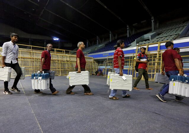 FILE PHOTO: Members of election staff carry Electronic Voting Machines (EVM) and Voter Verifiable Paper Audit Trail (VVPAT) machines after collecting them from a distribution centre at an indoor stadium ahead of the seventh and last phase of general election, in Kolkata, India, May 18, 2019.