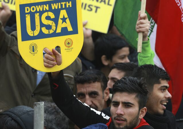 A demonstrator holds an anti-U.S. placard during a ceremony celebrating the 40th anniversary of the Islamic Revolution, at the Azadi, Freedom, Square in Tehran, Iran, Monday, Feb. 11, 2019
