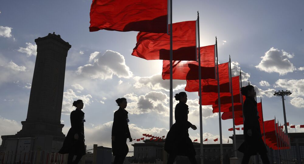 Bus ushers walk past red flags on Tiananmen Square during a plenary session of the Chinese People's Political Consultative Conference (CPPCC) at the Great Hall of the People in Beijing, 11 March 2019