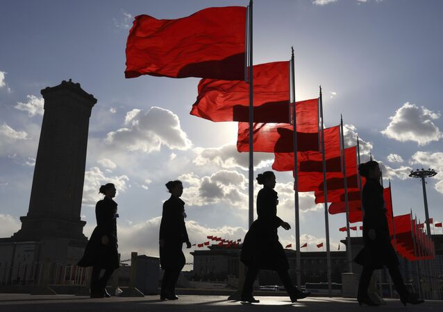 Bus ushers walk past red flags on Tiananmen Square during a plenary session of the Chinese People's Political Consultative Conference (CPPCC) at the Great Hall of the People in Beijing Monday, March 11, 2019