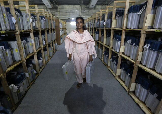 An election staff member carries Electronic Voting Machines (EVM) after collecting them from a distribution centre at an indoor stadium ahead of the seventh and last phase of general election, in Kolkata, India, May 18, 2019