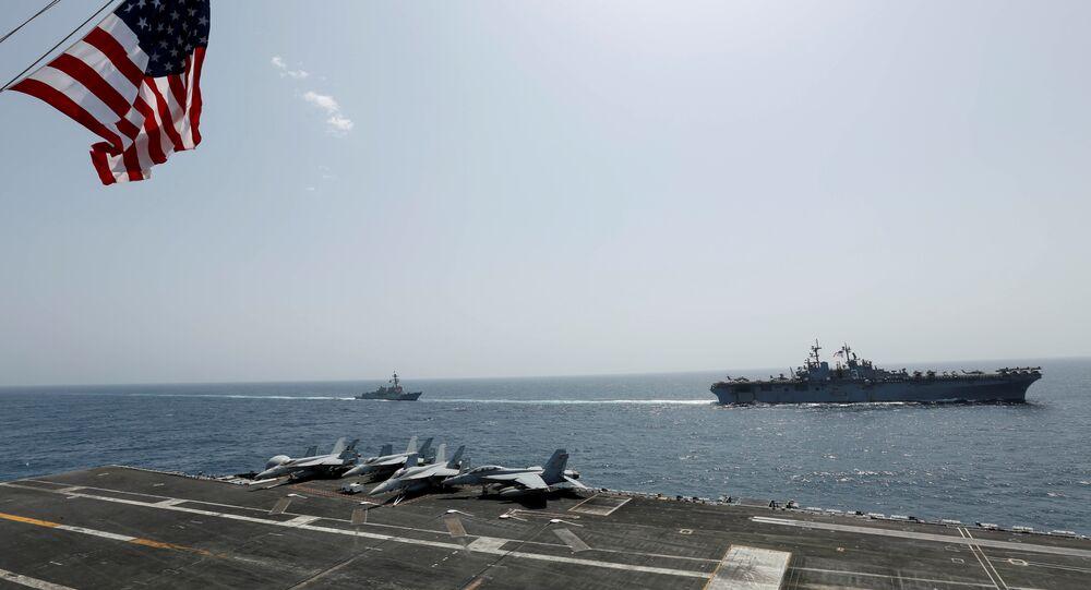 The US Navy Wasp-class amphibious assault ship USS Kearsarge and the Arleigh Burke-class guided-missile destroyer USS Bainbridge sail alongside the Nimitz-class aircraft carrier USS Abraham Lincoln in the Arabian Sea
