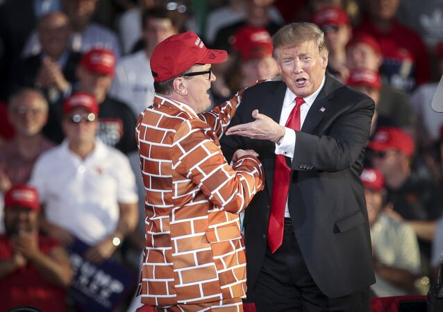 U.S. President Donald Trump calls up Blake Marnell, wearing a jacket with bricks representing a border wall, to the stage during a 'Make America Great Again' campaign rally at Williamsport Regional Airport, May 20, 2019 in Montoursville, Pennsylvania