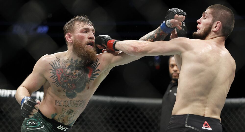 Conor McGregor, left, and Khabib Nurmagomedov throw punches during a lightweight title mixed martial arts bout at UFC 229 in Las Vegas, Saturday, Oct. 6, 2018