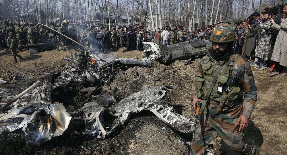An Indian army soldier walks past the wreckage of an Indian helicopter after it crashed in Budgam area on the outskirts of Srinagar in Indian-controlled Kashmir, 27 February 2019