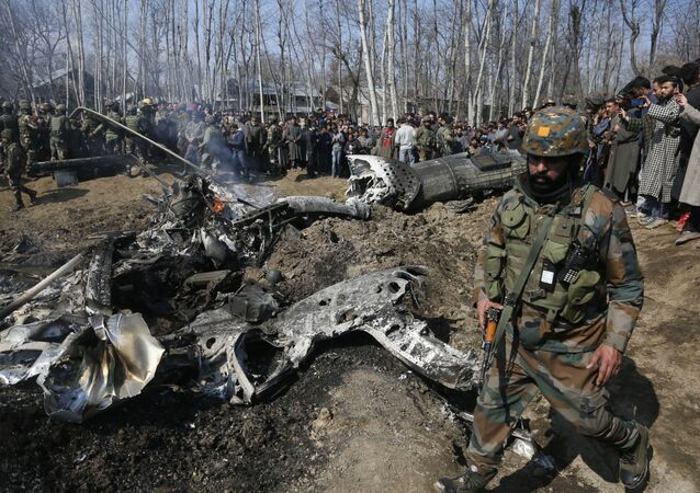 An Indian army soldier walks past the wreckage of an Indian helicopter after it crashed in Budgam area, outskirts of Srinagar, Indian controlled Kashmir, Wednesday, Feb.27, 2019