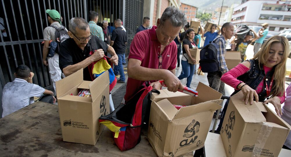 In this July 6, 2018 photo, employees of a government-supported cultural center collect their boxes with subsided food distributed under government program named CLAP in downtown Caracas, Venezuela. Everyone from museum curators to janitors waited in line to sign a clipboard before government loyalists hand over the box of food.