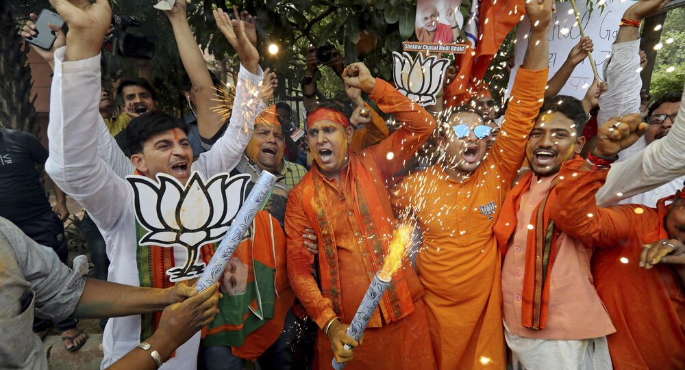 Bharatiya Janata Party (BJP) workers celebrate outside BJP headquarters in New Delhi India, Thursday, May 23, 2019