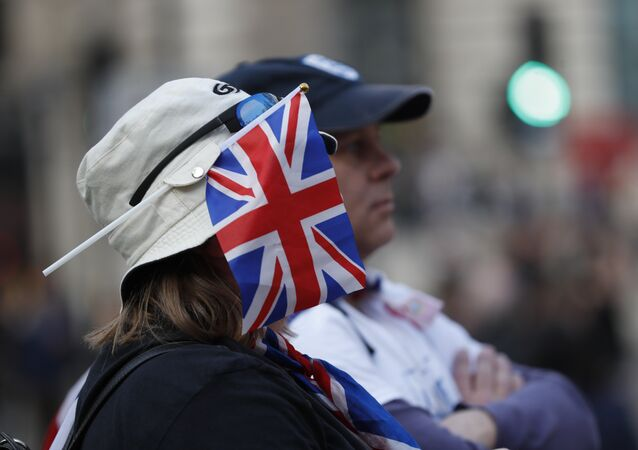 A protester wears a British union flag as people gather near parliament during Brexit demonstrations in London, Friday March 29, 2019.