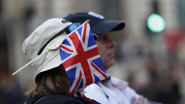 A protester wears a British union flag as people gather near parliament during Brexit demonstrations in London, Friday March 29, 2019. - Sputnik International