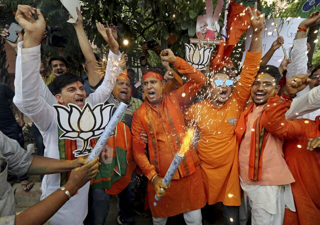 Bharatiya Janata Party (BJP) workers celebrate outside BJP headquarters in New Delhi India, Thursday, May 23, 2019.