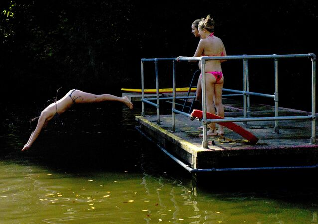 A woman dives into the cold water of the mixed pond during unseasonal hot weather on Hampstead Heath in London, Thursday, Sept. 28, 2011
