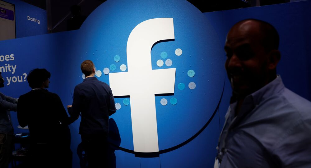 Attendees walk past a Facebook logo during Facebook Inc's F8 developers conference in San Jose, California, U.S., April 30, 2019