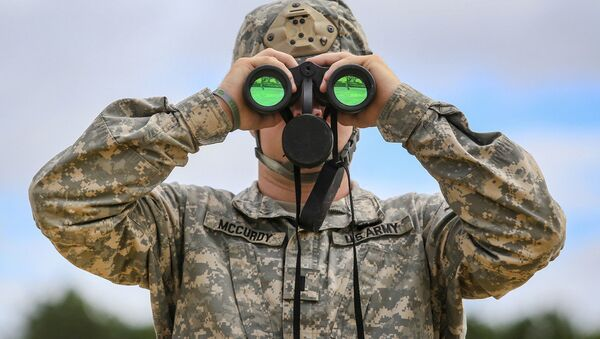 Army 1st Lt. James McCurdy uses binoculars to observe targets down range while his soldiers fire MK 19 grenade launchers during training at Joint Base McGuire-Dix-Lakehurst, N.J., July 26, 2018 - Sputnik International