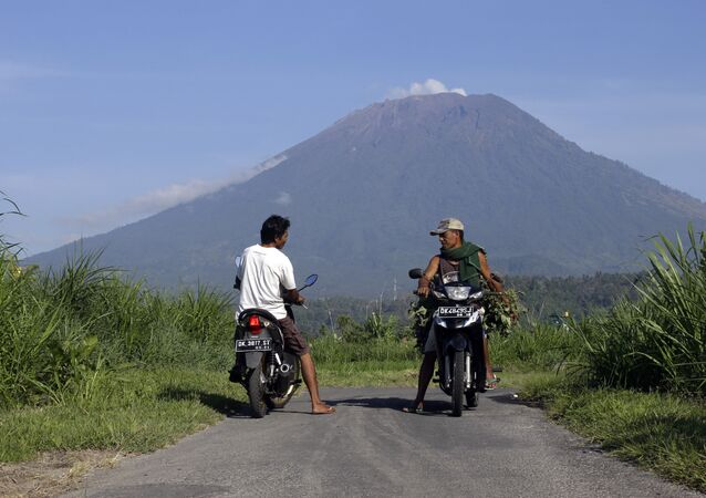Villagers on their motorcycles talk each other with Mount Agung volcano in the background in Karangasem, Bali, Indonesia, Wednesday, Oct. 25, 2017