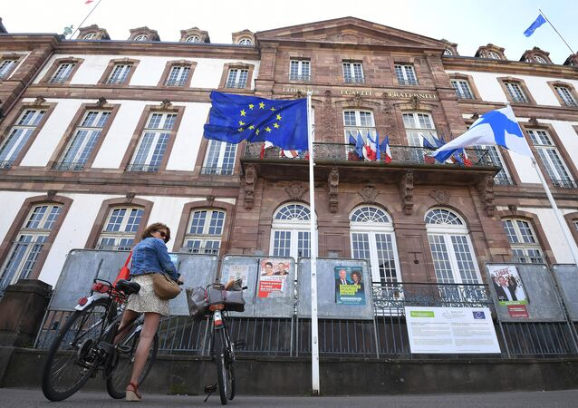 This picture taken on May 26, 2019 shows a woman on a bicycle standing in front of a European flag during the European Parliament elections at a polling station in Strasbourg, eastern France.