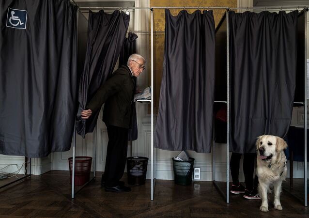 A person is seen in a polling booth during the vote for the European parliament elections, on May 26, 2019 in Le Puy-en-Velay.
