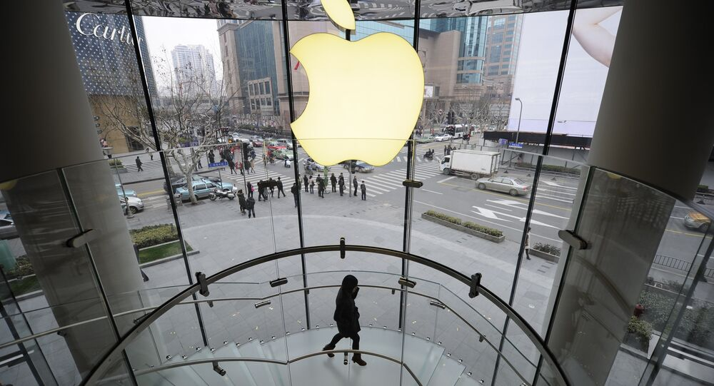 A customer walks under an Apple logo sign at an Apple shop in Shanghai on February 22, 2012