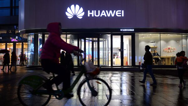 A woman cycles past a Huawei store in Shenyang, Liaoning province, China on 20 March 2019 - Sputnik International