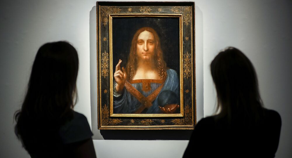 Christie's employees pose in front of a painting entitled Salvator Mundi by Italian polymath Leonardo da Vinci at a photocall at Christie's auction house in central London on October 22, 2017 ahead of its sale at Christie's New York on November 15, 2017