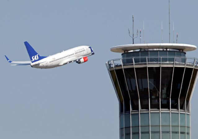 A Scandinavian SAS airline passenger plane flies near the air traffic control tower after taking off from Charles de Gaulle International Airport in Roissy, near Paris, August 21, 2013