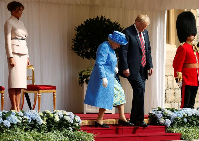 The First Lady Melania Trump waits as U.S. President Donald Trump and Britain's Queen Elizabeth walk across the courtyard to inspect the Coldstream Guards during a visit to Windsor Castle in Windsor