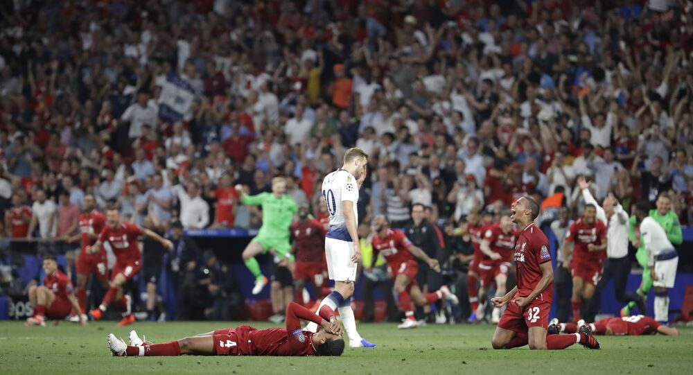 Tottenham's Harry Kane walks past Liverpool's players as they celebrate after winning the Champions League final soccer match against Tottenham Hotspur at the Wanda Metropolitano Stadium in Madrid, Saturday, June 1, 2019.