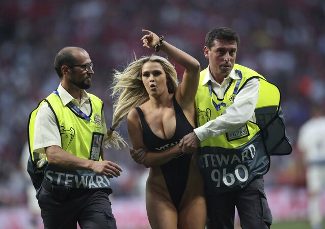 Kinsey Wolanski, a woman that has invaded the pitch is taken away by security during the Champions League final soccer match between Tottenham Hotspur and Liverpool at the Wanda Metropolitano Stadium in Madrid, Saturday, June 1, 2019.
