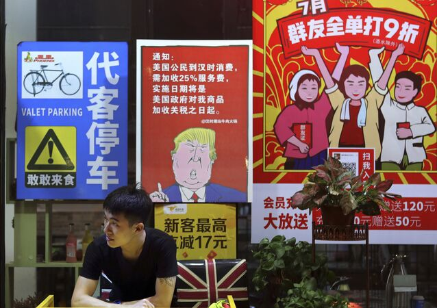 A man stands near a poster depicting a mural of U.S. President Donald Trump stating that all American costumers will be charged 25 percent more than others starting from the day president Trump started the trade war against China, on display outside a restaurant in Guangzhou in south China's Guangdong province.