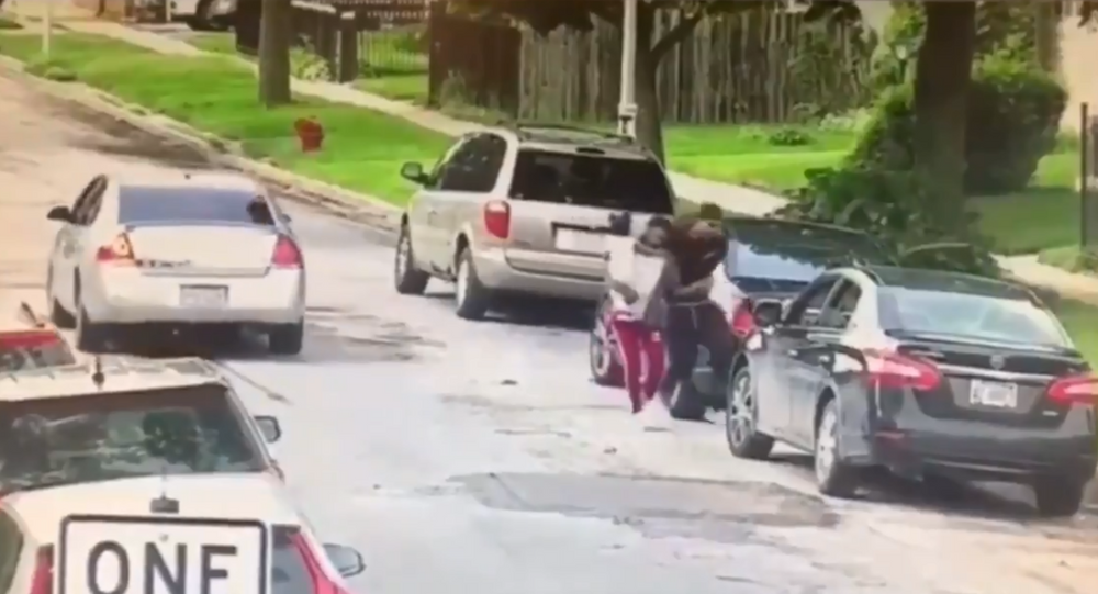 Leaked surveillance footage shows fatal shooting of Brittany Hill, a 24-year-old Chicago resident who hid behind a car and shielded her 1-year-old daughter during a drive-by shooting.