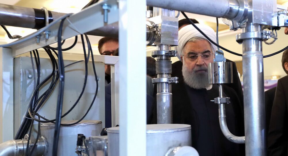 Hassan Rouhani on April 9, 2018 shows him (C) during a ceremony to mark National Nuclear Technology Day in Tehran