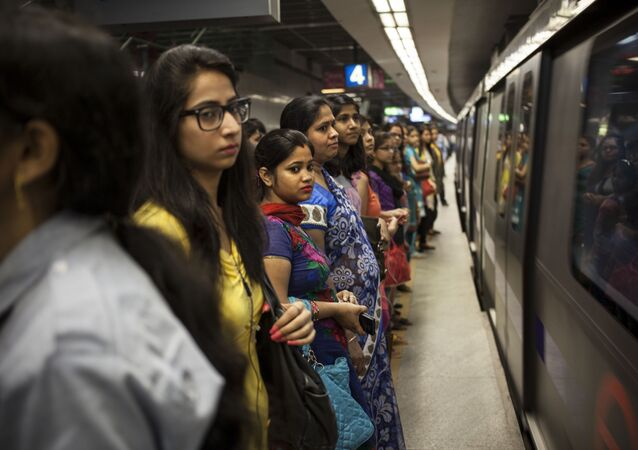 Commuters wait to board a women only compartment of a metro in New Delhi, India, Thursday, June 26, 2014