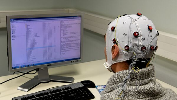 A picture taken on November 20, 2017 at the GIPSA-lab at the CNRS of Grenoble shows a researcher using a Brain-Computer-Interface helmet Brain Invaders which enables to select symbols without motor command - Sputnik International