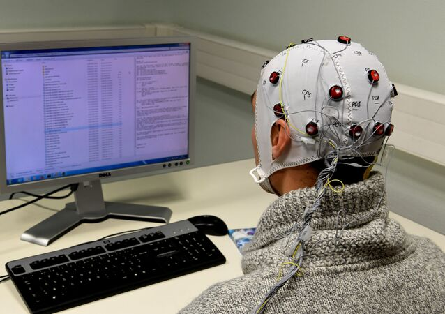 A picture taken on November 20, 2017 at the GIPSA-lab at the CNRS of Grenoble shows a researcher using a Brain-Computer-Interface helmet Brain Invaders which enables to select symbols without motor command