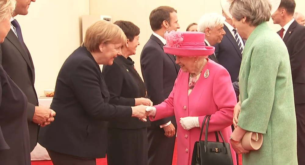 British Queen Elizabeth II shakes hands with German Chancellor Angel Merkel at a ceremony commemorating the 75th anniversary of the D-Day landings