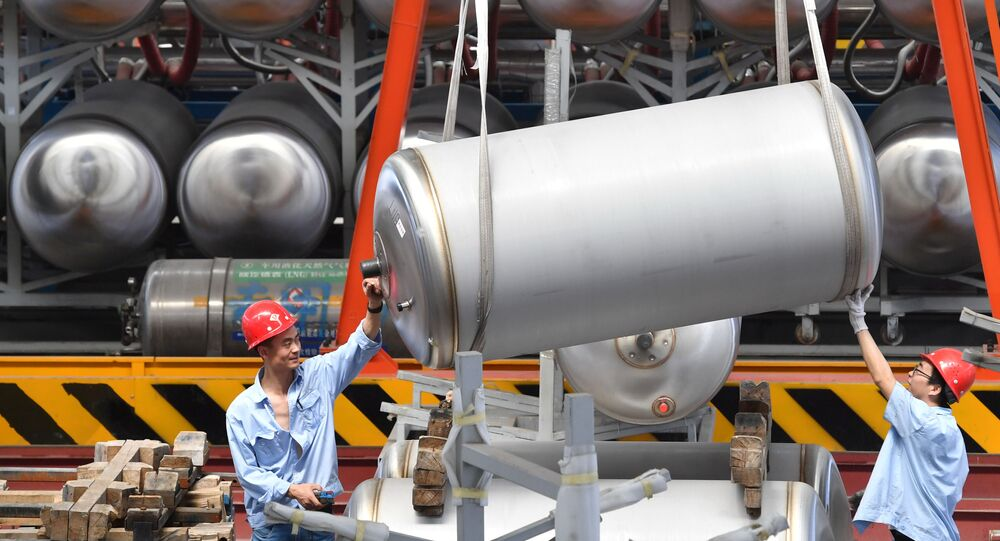 Employees work next to tanks for liquefied natural gas (LNG) at a factory in Xian, Shaanxi province, China June 3, 2019