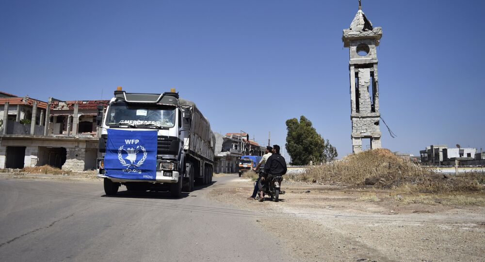 An aid truck of the UN World Food Programm (WFP) drives past destroyed buildings the town of Al-Houla, on the northern outskirts of Homs in central Syria, on May 25, 2016