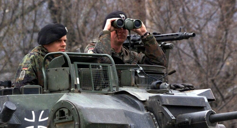 A German officer of the NATO contingent deployed in Macedonia looks through his binoculars