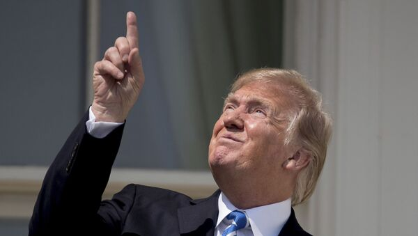 President Donald Trump points to the sun as he arrives to view the solar eclipse, Monday, Aug. 21, 2017, at the White House in Washington. - Sputnik International